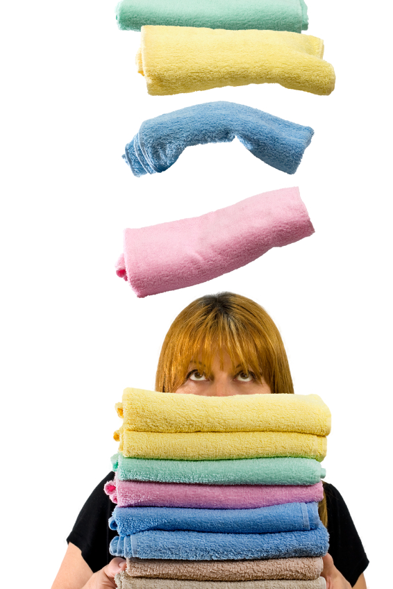 Housewife holding towels on white background